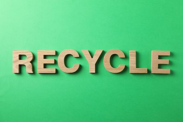 Reciclar feito de letras de madeira sobre fundo verde, vista superior