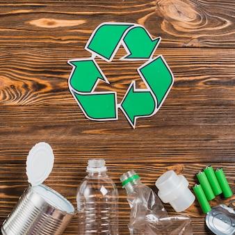 Reciclar o ícone com o produto de reciclagem no cenário texturizado de madeira
