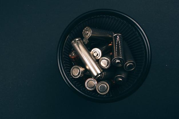 Reciclar, reutilizar, reduzir o conceito. proteger um ambiente. baterias de prata de uso único na caixa de metal no fundo escuro, close-up. lixo elétrico descartável.