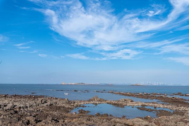 Recife amarelo e mar sob o céu azul