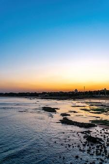 Recife costeiro da cidade e paisagem do pôr do sol