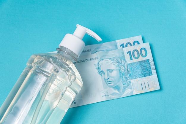 Recipiente com álcool gel e dinheiro real brasileiro,