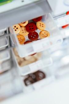 Recipiente de armazenamento de plástico com botões de madeira para o design de pano