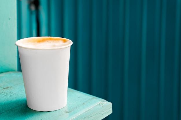 Recipiente de café de papel no fundo azul bebida para viagem