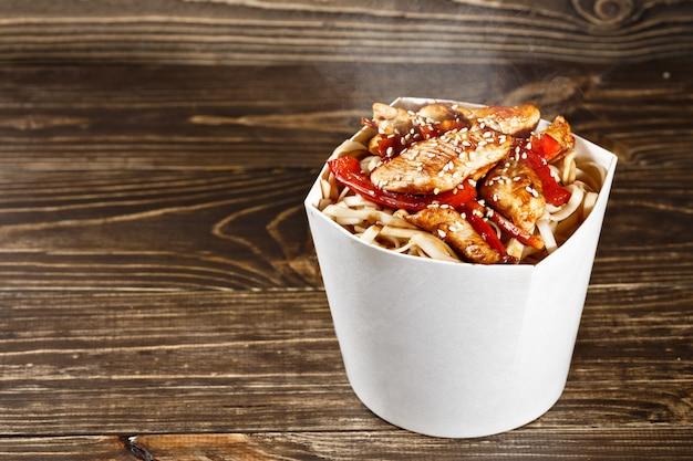 Recipiente de caixa de macarrão delicioso wok com udon e frango na mesa de madeira. fast food chinês e asiático para viagem.