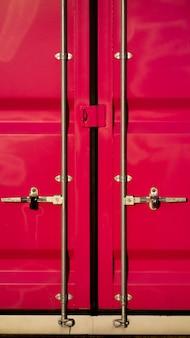 Recipiente de carga rosa para transporte com porta fechada.