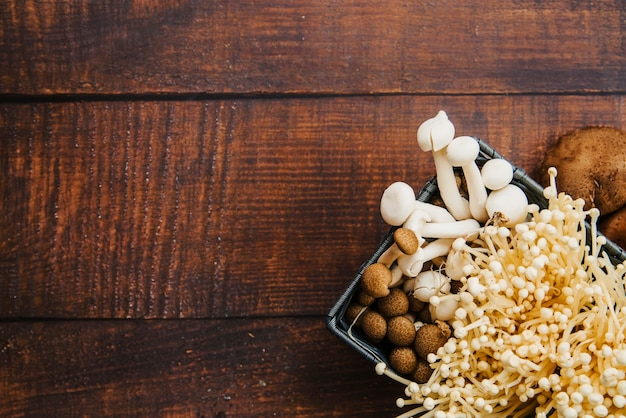 Recipiente de cogumelos na mesa de madeira