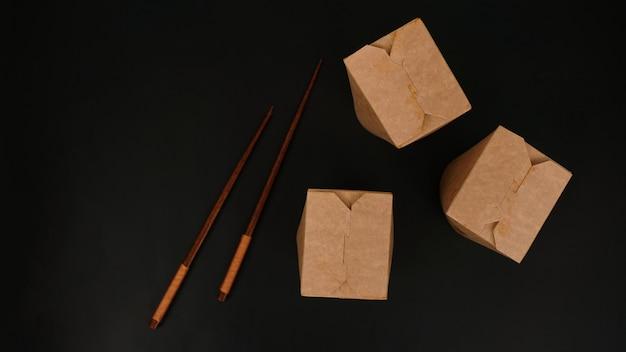 Recipiente de comida de papelão de papel marrom em fundo preto. entrega de comida asiática. embalagem wok