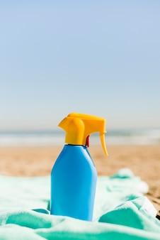 Recipiente de cosméticos protetor solar azul fechado na manta turquesa na praia