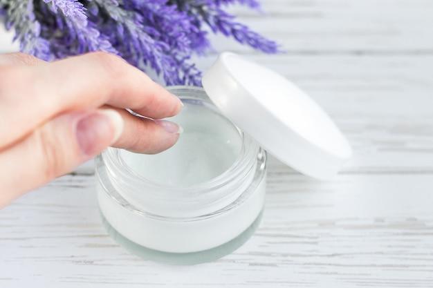 Recipiente de creme cosmético em fundo branco de madeira com flores