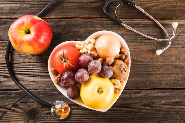 Recipiente de forma de coração com comida saudável perto de estetoscópio em fundo de madeira