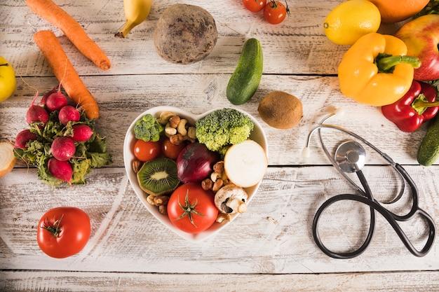Recipiente de forma de coração com legumes saudáveis perto de estetoscópio