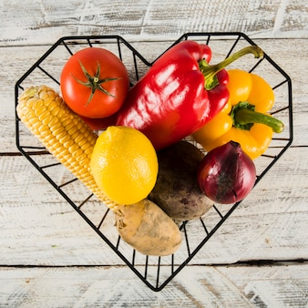 Recipiente de forma de coração com vegetais crus coloridos sobre fundo de madeira