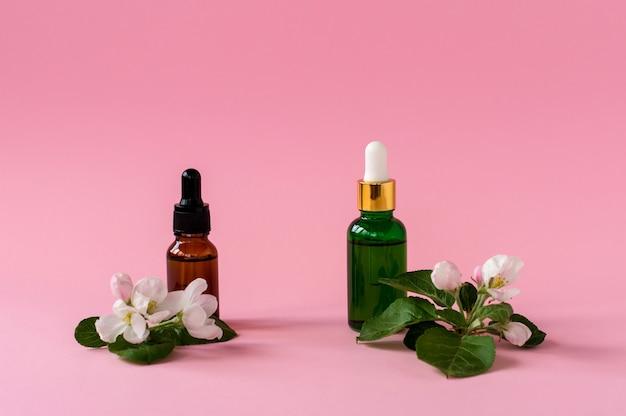 Recipiente de garrafa de skincare natural com folha verde, ingredientes de flores em fundo rosa. remédio caseiro e conceito de produto de beleza.