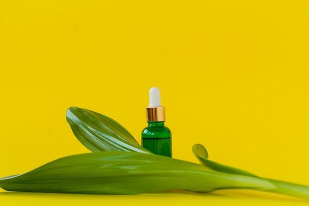 Recipiente de garrafa de skincare natural e folha verde orgânica em fundo amarelo. remédio caseiro e conceito de produto de beleza.