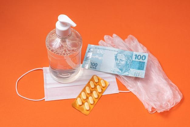 Recipiente de gel de álcool, máscara cirúrgica, remédio e dinheiro real brasileiro, na parede laranja