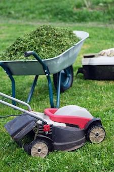 Recipiente de grama cortador de grama e um carrinho de mão de jardim cheio de grama aparada no gramado aparado