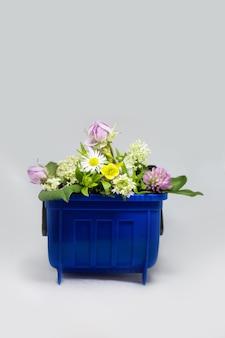 Recipiente de lata de lixo com flores, conceito ecológico de reciclagem