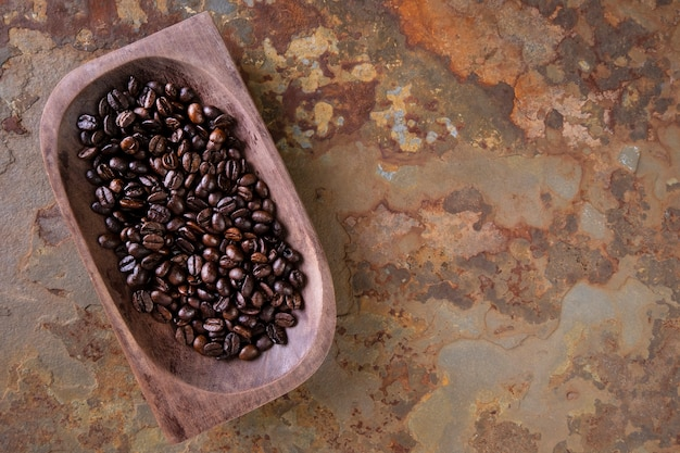Recipiente de madeira com grãos de café torrados em ardósia enferrujada.
