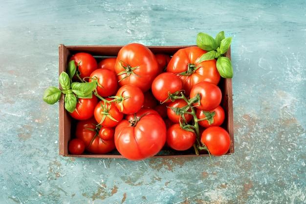 Recipiente de madeira com tomates colhidos frescos e maduros.