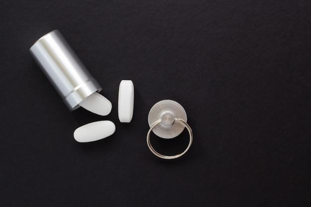 Recipiente de metal e comprimidos em um fundo preto, close-up