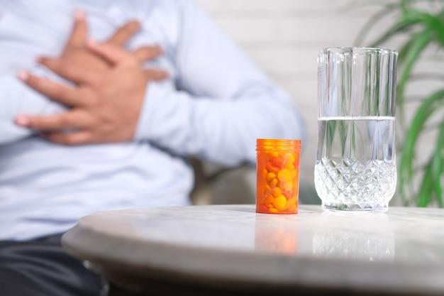 Recipiente de pílulas na mesa e um homem sofrendo de dor no coração no fundo