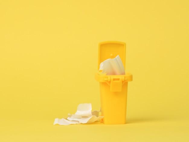 Recipiente de plástico amarelo para coleta de plástico e processamento posterior em um fundo amarelo, espaço de cópia