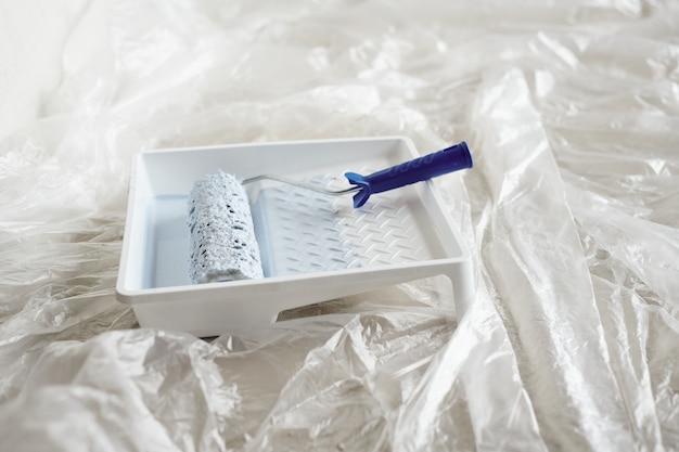 Recipiente de plástico quadrado branco com tinta e rolo no chão da sala de estar ou outro cômodo da nova casa ou apartamento durante a reforma da casa