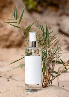 Recipiente de produto corporal na areia próximo à planta seca