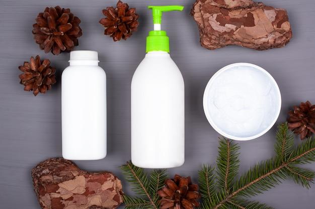 Recipiente de três brancos com cosméticos para cuidados com o corpo em um fundo cinza na vista superior do tema floresta