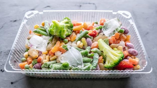 Recipiente de vegetais congelados em uma mesa cinza