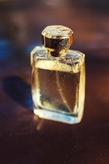 Recipiente de vidro com perfume coberto com gotas de água.