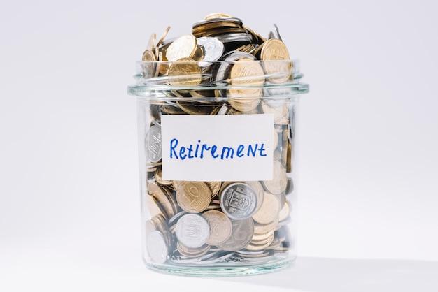 Recipiente de vidro de aposentadoria cheio de moedas no pano de fundo branco