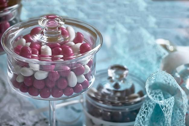 Recipiente de vidro para bombons coloridos usado como brinde de casamento e decoração de batismo católico.