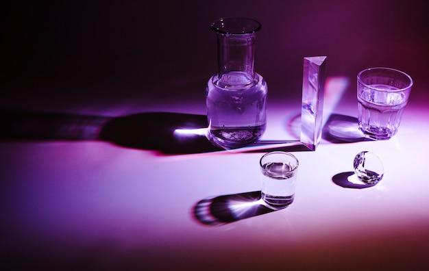Recipiente de vidro; prisma e diamante com sombra escura em fundo colorido
