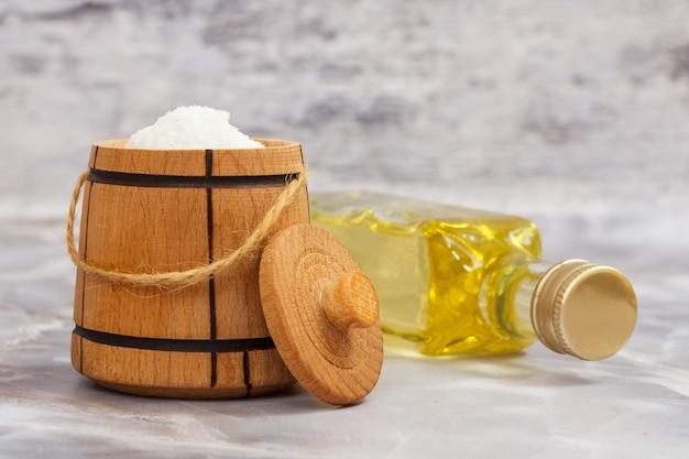 Recipiente para armazenar sal. adega de sal de madeira e uma garrafa de óleo de girassol na mesa da cozinha.