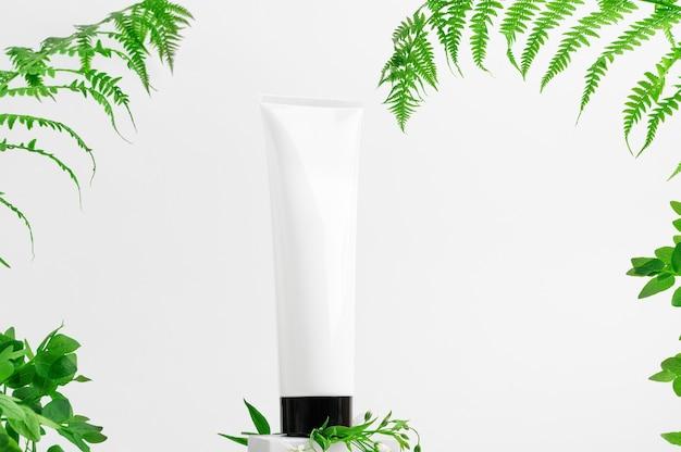 Recipiente sem marca no pedestal. frasco para loção, produtos de higiene. folhas de samambaia da floresta sobre fundo claro. tubo para cosméticos. estilo de maquete, copie o espaço. conceito ecológico e de beleza. isolado no branco.