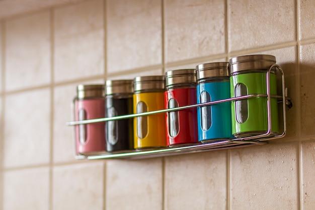 Recipientes coloridos de sal e pimenta de especiarias na cozinha