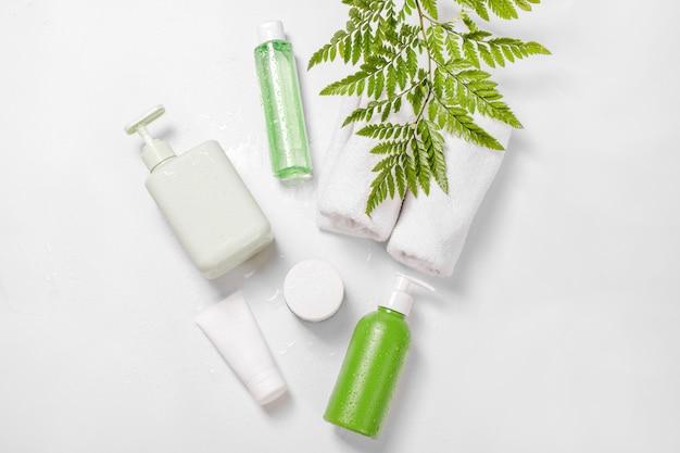 Recipientes cosméticos com folhas de ervas verdes e gotas de água