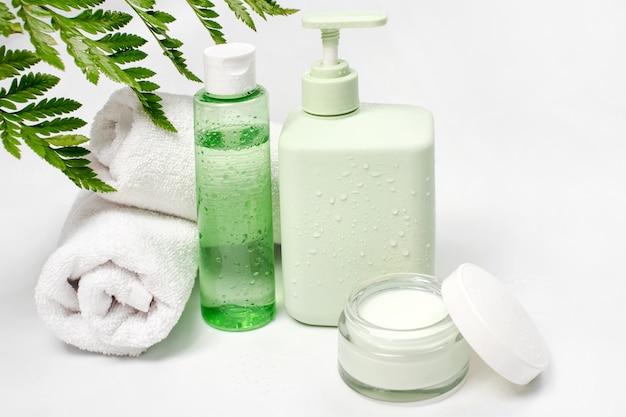 Recipientes cosméticos com folhas verdes de ervas, pacote de rótulo em branco para a marca. creme hidratante, sabonete líquido ou xampu, tônico, cuidados com a pele do rosto e do corpo. produto de beleza orgânico natural.