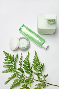 Recipientes cosméticos com folhas verdes de ervas, pacote de rótulo em branco para a marca. creme hidratante, sabonete líquido, tônico, cuidados com a pele do rosto e do corpo.
