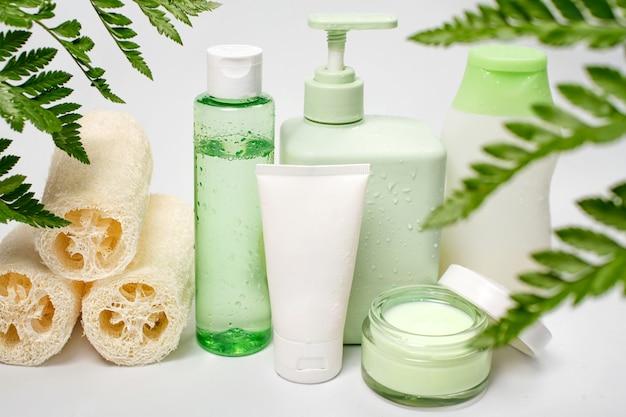 Recipientes cosméticos com folhas verdes de ervas, pacote de rótulo em branco para a marca. creme hidratante, shampoo, tônico, cuidados com a pele do rosto e do corpo.
