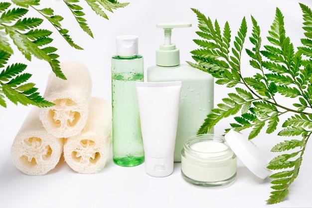 Recipientes cosméticos com folhas verdes de ervas, pacote de rótulo em branco para marcar a maquete. creme hidratante, shampoo, tônico, cuidados com a pele do rosto e do corpo. produtos de beleza orgânicos naturais.