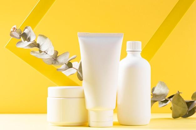 Recipientes cosméticos em fundo amarelo