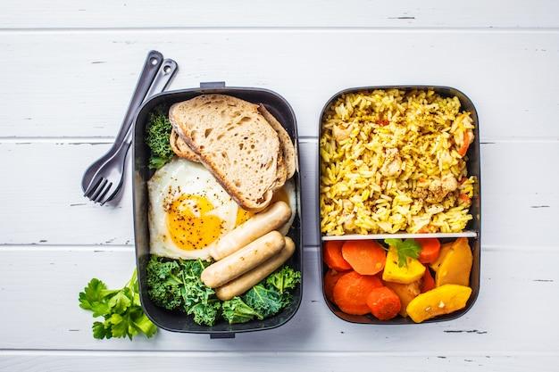 Recipientes da preparação da refeição com arroz com galinha, vegetais cozidos, ovos, salsichas e tiro aéreo da salada.