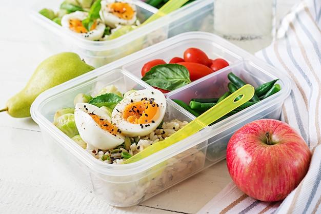 Recipientes da preparação da refeição do vegetariano com ovos, couves-de-bruxelas, feijões verdes e tomate.