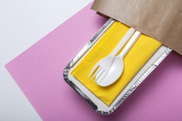 Recipientes de alumínio para levar alimentos preparados para entrega em sacos de papel recicláveis.