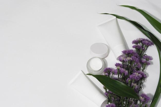 Recipientes de frasco cosmético branco produto com flor e folha.