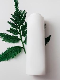 Recipientes de frasco cosmético com folhas verdes de ervas, rótulo em branco para branding, produto de beleza natural.