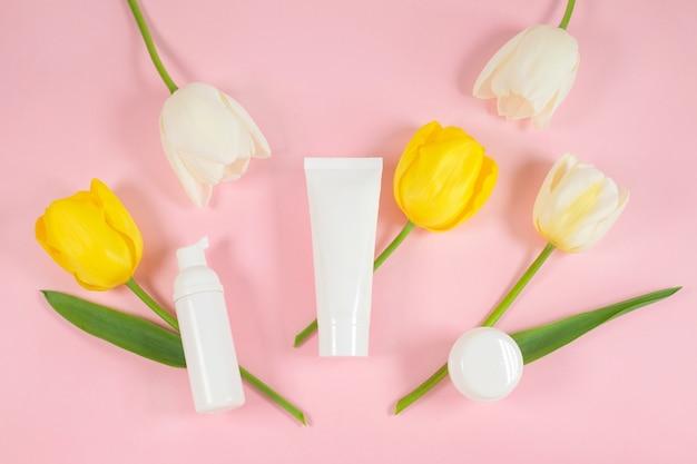 Recipientes de frascos de cosméticos brancos em flores amarelas e tulipas brancas